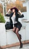 Η ελκυστική νέα γυναίκα με burgundy χρωμάτισε το μεγάλο καπέλο στο φθινοπωρινό πυροβολισμό μόδας Όμορφη κυρία στη μαύρη εξάρτηση  Στοκ Φωτογραφία
