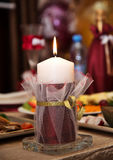 Burgundy candle on the table. Maroon beautiful embellished candle burns on the table Stock Photo