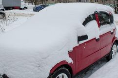 Burgundy car in the parking lot under the snow royalty free stock photos