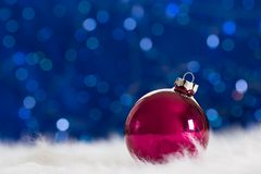 Burgundy Christmas ball on white fur with garland lights on blue Stock Images