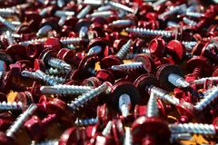Long texture a lot of dark burgundy color. Burgundy color, screw, bolt, metal, construction, cap, background, shiny, work, equipment, head, industry, steel stock photography