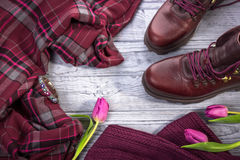 Burgundy color. Stylish shoes, clothes and tulips on a gray background.Top view Royalty Free Stock Image