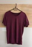 Burgundy fashionable T-shirt. Burgundy modern T-shirt on the hanger Royalty Free Stock Images