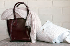 Burgundy handbag, scarf and rpundabout (jacket) on a wooden board against white brick wall Stock Photos