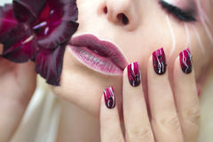 Burgundy manicure with gladiolus. Stock Photos
