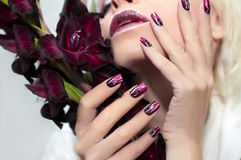 Burgundy manicure with gladiolus. Stock Photography