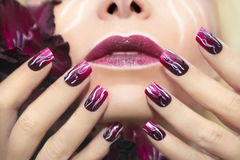 Burgundy manicure with gladiolus. Stock Image