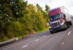 Burgundy modern semi truck and reefer trailer in straight wide h Royalty Free Stock Images
