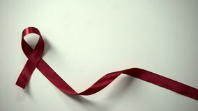 Burgundy ribbon in lady hands, multiple myeloma syndrome awareness, healthcare. Stock photo royalty free stock photography