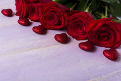 Burgundy roses and red glitter hearts on lilac background Stock Images