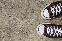 Burgundy sneakers on rough pavement with lots of room for copy royalty free stock images