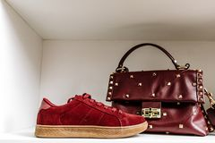 Burgundy suede sneakers with a beige sole and burgundy leather bag decorated with metal diamonds against a white shelf royalty free stock images