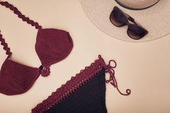Burgundy swimsuit, hat and sunglasses. Beach wardrobe. Fashionable concept royalty free stock photo