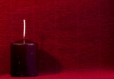 Burgundy wax candle on the red background paper, celebration Royalty Free Stock Images
