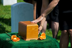 Burial Farewell. Mourners touch urn as final farewell at funeral at Arlington National Cemetery Stock Photo