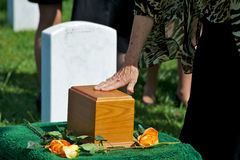 Burial Farewell. Mourners touch urn as final farewell at funeral at Arlington National Cemetery Royalty Free Stock Photo