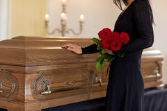Sad woman with red roses and coffin at funeral Royalty Free Stock Image