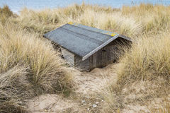 Buried Beach Hut. Beach Hut Buried in Sand Dunes at Brancaster, Norfolk, UK Royalty Free Stock Images