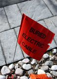 Buried Electric Cable Marker. Utility flag markers to alert of buried  electric lines on residential property Stock Images
