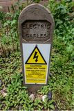 Buried electric cables identification and warning post stock photography