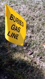 Buried Gas Line Marker. Yellow flag marking underground natural gas line in yard for safety reasons Royalty Free Stock Photo
