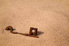 Buried key. A rusty old key buried in the sand Stock Photos