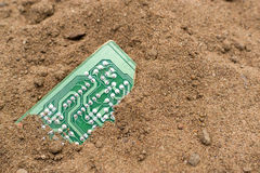Buried PCB board in Brown Sand Stock Image
