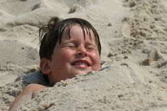 Buried in sand. Young boy buried in sand at the beach Stock Photography