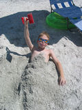 Buried in the Sand. Boy buried at the beach Royalty Free Stock Photo