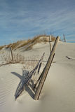Buried sand dune fence and post. Shifting sand dunes eventually bury fence and post making it an interesting feature as white sand gather around the posts Royalty Free Stock Photography