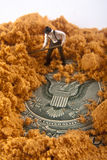 Buried Seal of the United States. Miniature man with partially covered seal of the United states buried in dirt stock image