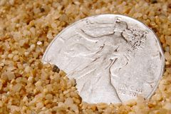 Buried treasure. Silver dollar peeks out of the sand inviting the keen eyed beachcomber Stock Photos