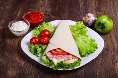 Burito con il prosciutto, il formaggio ed i pomodori fotografie stock libere da diritti