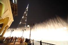 burj迪拜喷泉启用的晚上摩天大楼 免版税库存图片