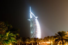 Burj Al Arab glowing at night. A night shot of the Burj al Arab with white lights beaming onto it illuminating it in the dark Stock Photo