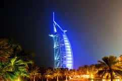 Burj Al Arab glowing at night in Blue. Burj Dubai illuminated in a blue light at night with a traditional dhow lit up on the water Royalty Free Stock Image