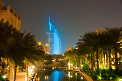 Burj Al Arab glowing at night in Cyan. Burj Dubai illuminated in a blue light at night with a reflection in the water royalty free stock image