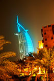 Burj Al Arab glowing at night in Cyan. A night scene showing palms and building with the Burj al Arab in the background in Dubai Royalty Free Stock Images