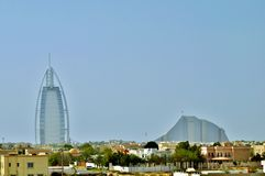 Burj al Arab and Jumeirah beach Hotel in Dubai. Low Arab houses and villas in yellow, beige and white colors in front of city's famous landmarks: Burj al Arab Royalty Free Stock Images