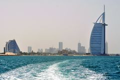 Burj al Arab and Jumeirah beach Hotel seen from sea. Burj al Arab and Jumeirah Beach Hotel, viewed from the boat which leaves curved white foam trace in the Royalty Free Stock Images