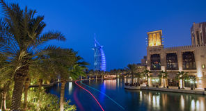 Burj Al Arab at night. Burj Dubai illuminated in a blue light at night with trailing lights of a boat Stock Images