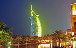 Burj Al Arab at night in Green 2. A night scene of a boat and palm trees with the Burj al Arab glowing in green Royalty Free Stock Images
