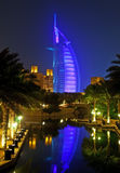 Burj Al Arab at night with reflection. A night shot of the Burj al Arab with purple lights illuminating it and its reflection in the water Royalty Free Stock Photos