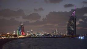 Burj Al Arab och Jumeirah sätter på land hotellet på solnedgången stock video