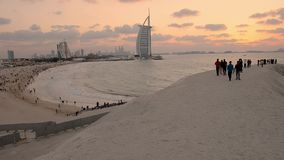 Burj Al Arab och Jumeirah sätter på land hotellet på solnedgången lager videofilmer