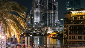 Burj Khalifa and Dubai Fountain at night timelapse. The Dubai Fountain is the world's largest choreographed fountain. Burj Khalifa and Dubai Fountain with boats stock footage
