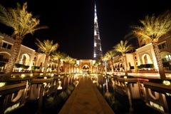 Burj rua de Dubai, Dubai da noite com palmas e associação Fotografia de Stock Royalty Free