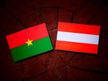 Burkina Faso flag with Austrian flag on a tree stump  Stock Photo