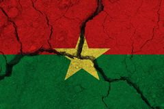 Burkina Faso flag on the cracked earth. National flag of Burkina Faso. Earthquake or drought concept royalty free stock photography