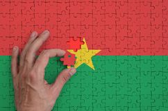 Burkina Faso flag is depicted on a puzzle, which the man`s hand completes to fold.  royalty free illustration